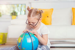Pretty child girl at home dreaming of travel and tourism, explor Royalty Free Stock Photos