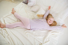 Pretty child girl is lying down in the white bed Stock Photo