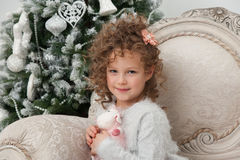 Pretty child girl with sheep toy and Christmas tree Royalty Free Stock Photos