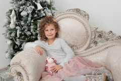 Pretty child girl with sheep toy near Christmas tree Royalty Free Stock Image