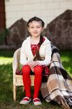 Pretty child girl sitting in a garden Royalty Free Stock Photo