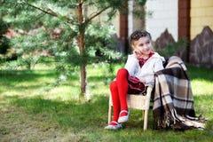 Pretty child girl sitting in a garden Stock Image