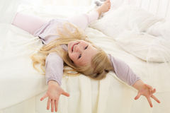 Pretty child is lying down on bed with white sheets Royalty Free Stock Images