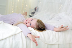 Pretty child is lying down in the white bed Stock Photography