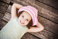 Lying child. Pretty child lying on wooden surface Royalty Free Stock Photo