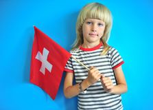 Pretty child with a national flag of Switzerland. Portrait of blonde long hair kid indoors Royalty Free Stock Images