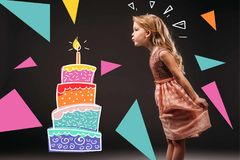 Pretty child in pink dress blowing drawn candle on birthday cake,. Isolated on grey Royalty Free Stock Photography