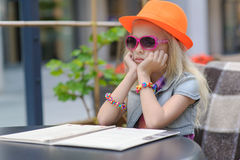 Pretty child reading menu in the cafe Stock Images