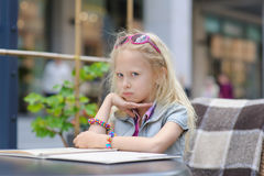 Pretty child reading menu in the cafe Stock Photos