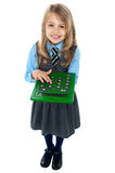 Pretty child in school uniform using calculator. Aerial view of pretty schoolgirl in studio pressing key 6 on calculator Royalty Free Stock Photos