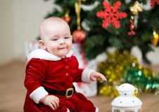 Pretty child sitting in front of Christmas tree Stock Image