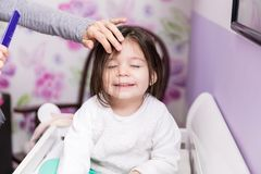 Mom Combing Daughter`s Hair. Pretty child smiling while mother grooming her hair at home royalty free stock images