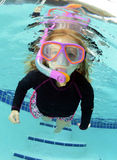 Pretty child swimming in pool. Cute child swimming in pool with goggles and snorkel stock photos