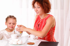 Pretty child and young girl drinking tea Stock Images