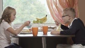 Pretty children eat spaghetti in the kitchen stock video footage
