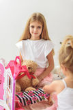 Pretty children entertaining with toy house royalty free stock image