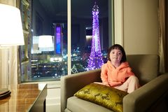 Little girl in hotel room with Eiffel Tower night scene outside