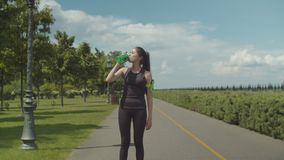 Fit woman drinking energy drink after hard workout. Pretty chinese female runner having energy drink while walking along city park lane on sunny morning. Fit stock footage
