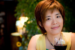 Pretty chinese girl. Drinking red wine in a restauant Royalty Free Stock Images