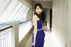 Pretty Chinese girl with blue full dress. In corridor Stock Photo