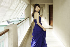 Pretty Chinese girl with blue full dress. In corridor Royalty Free Stock Images