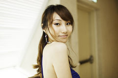 Pretty Chinese girl with blue full dress. In corridor Royalty Free Stock Photo