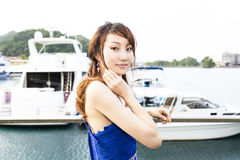 Pretty Chinese girl with blue full dress. With yacht Royalty Free Stock Image