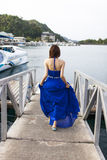 Pretty Chinese girl with blue full dress. With yacht Royalty Free Stock Photography