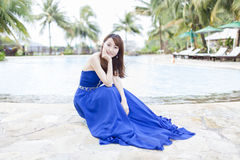 Pretty Chinese girl with blue full dress. With swimming pool Stock Photo