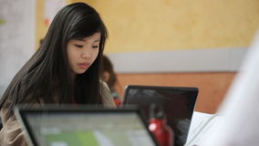 Pretty chinese woman works on personal computer in studio. She is serious and calm, business lady is concentrated on her occupation that even does not notice stock footage