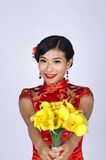 Pretty chinese young woman holding a bunch of yellow daffodils Stock Image