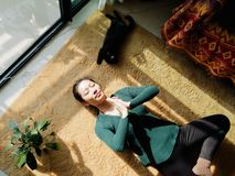 Pretty Chinese young woman meditating at home, lying on floor with her black cat in sun light stock image