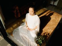 Pretty Chinese young woman meditating at home, sitting on floor with furry cushion in sun light royalty free stock photo