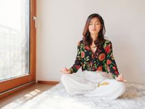 A pretty Chinese young woman practicing yoga at home, sitting on floor with furry cushion near sunny glass door, exercise royalty free stock image