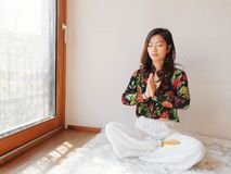 A pretty Chinese young woman practicing yoga at home, sitting on floor with furry cushion near sunny glass door, exercise stock images