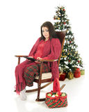 Pretty Christmas iPad User. A beautiful teen girl snuggled up in her pajamas and a blanket while working on her ipad.  A basketful of ornaments are nearby with a Royalty Free Stock Photos