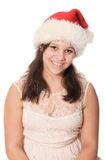 Pretty Christmas preteen girl. Pretty preteen girl wearing a red Santa Claus hat isolated on a white background Royalty Free Stock Image