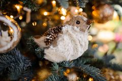 Pretty Christmas tree decoration toy in the form of a bird. Pretty Christmas tree decoration toy in the form of cute bird on the background of sparkling fir tree Stock Image