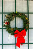Pretty Christmas wreath. With red bow on window Royalty Free Stock Images