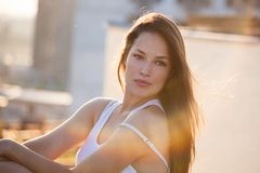 Pretty city girl portrait at sunset backlight at top of building royalty free stock image