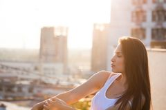 Pretty city girl profile portrait at sunset backlight at top of stock photo