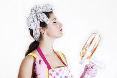 Pretty cleaning lady refreshing herself. With a fan royalty free stock photography