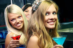 Pretty club girls. Three girls with martini glasses looking at camera and smiling Royalty Free Stock Images