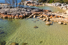 Pretty Coastal scene with turquoise waters rippled, rocky coastl. Pretty Coastal scene with turquoise waters rippled and sparkled, orange lichen growing on Royalty Free Stock Photo