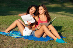 Pretty college girls. Studying outdoors on a campus field Stock Images