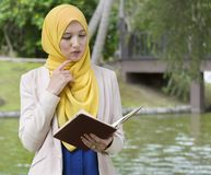 Pretty college student enjoy reading in the park Stock Photos