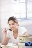 Pretty college student learning at home smiling royalty free stock photography