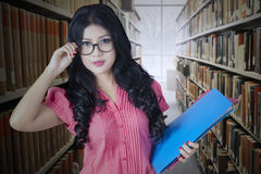 Pretty college student in library aisle Royalty Free Stock Images