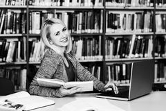 Pretty College Student in a Library. Portrait of an Attractive Student Doing Some School Work With a Laptop in the Library Stock Photography