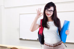 Pretty college student with OK sign in class Royalty Free Stock Photo